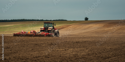 Fototapeta agricultural industrial landscape. a modern tractor with a trailed cultivator works on a hilly field before the autumn sowing campaign obraz
