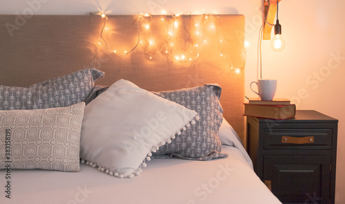 Confortable y cálida habitación para relajarse antes de irse a dormir. Vista frontal de cama de sábanas blancas junto a una negra mesa de luz con libros antiguos y taza de cerámica blancas.