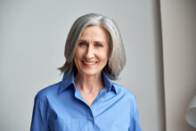 Smiling Sophisticated Mature Grey-haired Woman Standing On Grey Wall Background At Home. Happy Elegant Middle Aged Old Lady Professional Businesswoman Entrepreneur Posing In Office, Headshot Portrait.