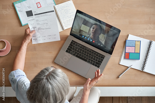 Fototapeta Mature senior employer hr checking indian female job applicant cv holding social distance remote online job interview by video conference call virtual chat meeting with recruit on laptop, top view. obraz