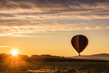 Hot Air Balloon In Colorful Rainbow Stripes Begins Ascent Over Farm Field As Sun Rises Golden Sky