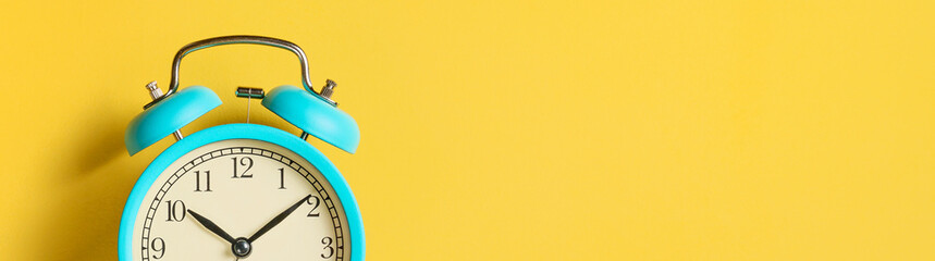Alarm clock on yellow background, banner. Front view. Copy space.