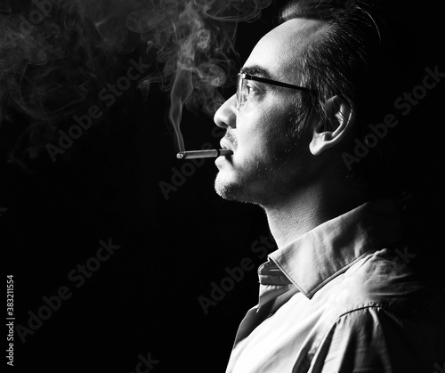 Fototapeta Portrait of brutal strong man business shark in official shirt and glasses stands with cigarette in his mouth