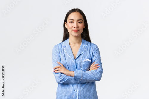 Confident and enthusiastic pretty asian girl in blue pajamas smiling at camera and cross arms chest with determined ready expression Canvas Print