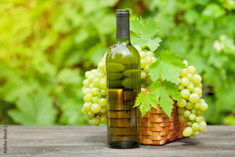 White wine bottle and ripe grape