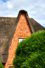 Pointed High Gable Of A House With Thatched Roof Behind A Green Bush, Sylt, Germany