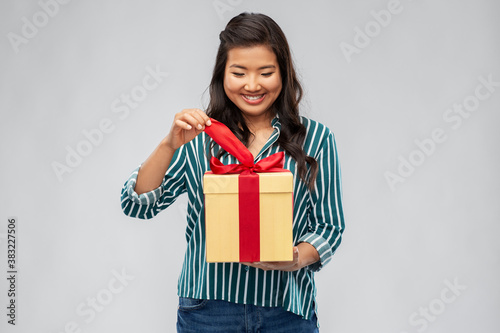 birthday present and surprise concept - happy asian young woman opening gift box Canvas