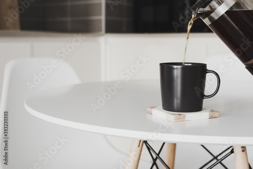 Black coffee brewed in a french press coffee maker pouring into a black mug Canvas