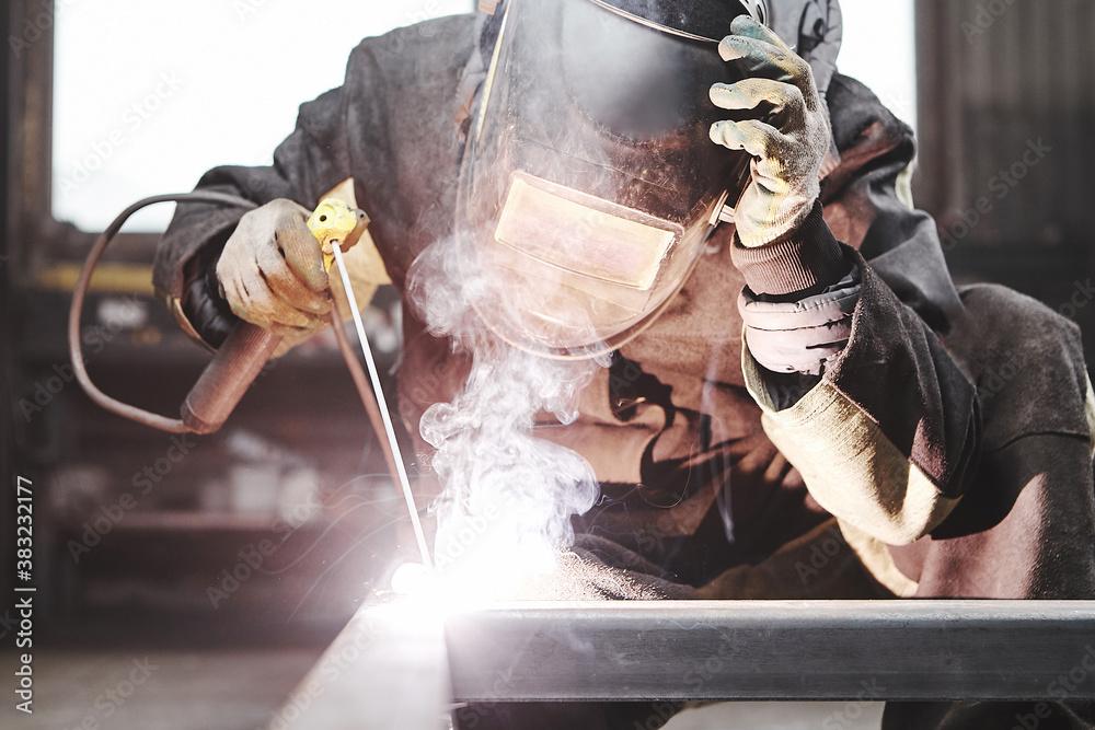 Fototapeta Man in protective mask welding metal construction.