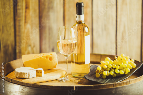 White wine in glass, bottle with grape and cheese on barrel front wood wall background Tapéta, Fotótapéta