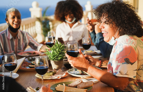 Young multiracial people eating and drinking red wine while wearing protective masks - Happy friends having fun doing dinner at restaurant patio - Social distance concept - Focus on right girl face