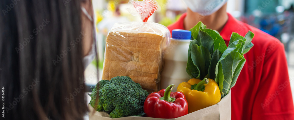Fototapeta Panoramic banner. food delivery service man wearing protection face mask handing fresh food set bag to young woman customer receiving order from courier at home, food delivery, online shopping concept