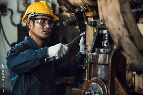 Foto Asian engineer mechanic man checking and using wrench for maintenance pressing m
