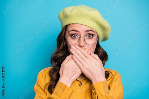Fototapeta Close up photo of astonished girl share friends secret close cover hands mouth lips stare stupor wear yellow good look outfit isolated over blue color background obraz