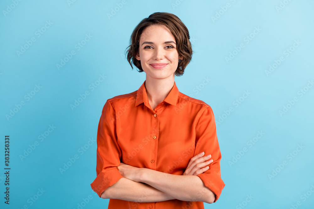 Fototapeta Photo of attractive charming lady cute bobbed hairdo arms crossed self-confident person worker friendly smile good mood wear orange office shirt isolated blue color background