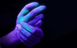 Washing hands in UV ultra violet light illustrating bacteria and viruses on hands and the importance of good hygiene. Covid 19 pandemic concept.