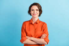 Photo Of Attractive Charming Lady Cute Bobbed Hairdo Arms Crossed Self-confident Person Worker Friendly Smile Good Mood Wear Orange Office Shirt Isolated Blue Color Background