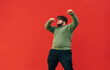 canvas print picture - Curly overweight young man in casual clothes dancing and listening to music on headphones, isolated. Fat man shows a dance performance on the street on a background of a red wall.