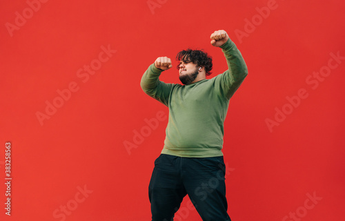 Fototapeta Curly overweight young man in casual clothes dancing and listening to music on headphones, isolated. Fat man shows a dance performance on the street on a background of a red wall. obraz