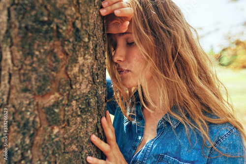Cuadros en Lienzo Closeup image of an young woman wearing a blue denim shirt hugs a big tree, posing on nature background