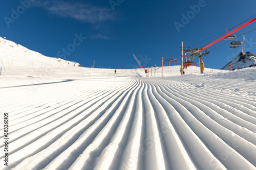 Close-up straight line rows of freshly prepared groomed ski slope piste with bright shining sun and clear blue sky background Billede på lærred