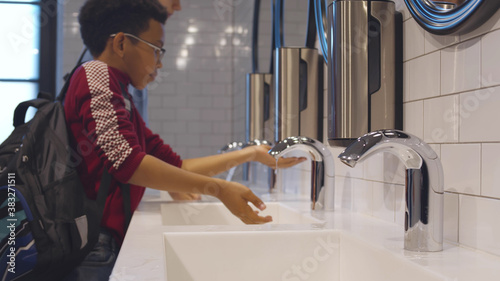 Foto Close up side view of diverse school pupils washing hands in lavatory