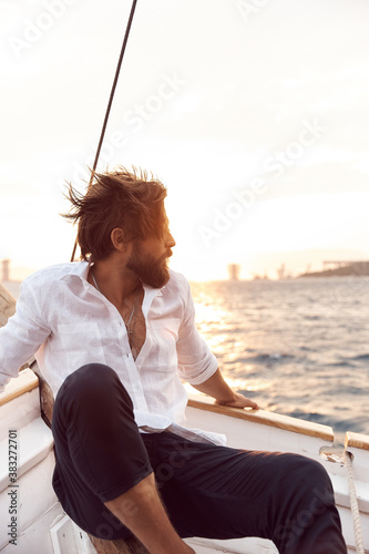 handsome man with a beard at sunset on a yacht wearing a white linen shirt and pants with a brutal expression