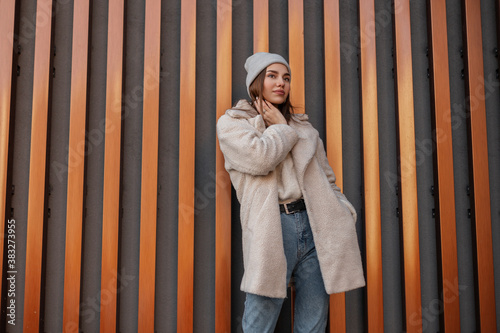 Obraz na plátně Young cute woman in a vintage knitted hat in blue jeans in a fashionable faux fur coat poses in the city near a modern metal wall
