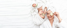 Positive Mother And Daughter Doing Face Mask Applying Pieces Of Cucumber To Their Eyes, Wrapped In A White Bath Towel, Facial Skin Care, Cosmetology And Spa, Long Banner Format. Space For Text