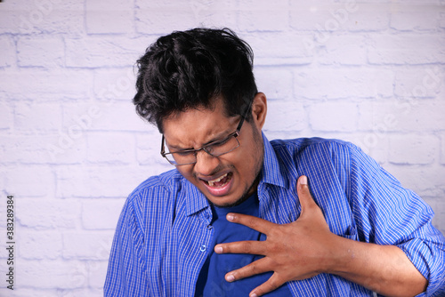 Fotomural young man suffering pain in heart and holding chest with hand