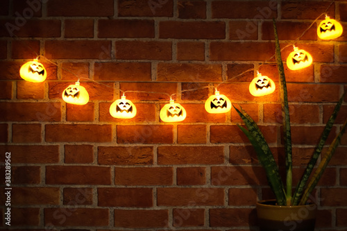 Fototapeta Halloween pumpkin string lights glowing , hanging on brick wall with house plant decoration