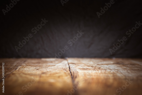 Dark background and vintage wooden table in the foreground Canvas Print