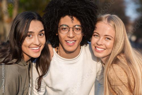 Obraz na plátně Close up portrait of international friends trio smiling at camera