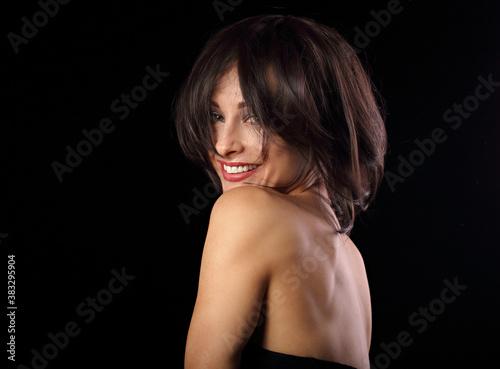 Beautiful happy laughing bright makeup woman shaking her black short hair on black background Fotobehang