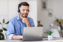 Business Education. Handsome Businessman In Headset Watching Webinar On Laptop In Office