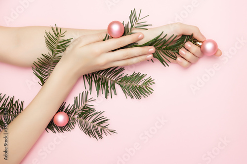 Fototapeta Close up beautiful womans hands holding a Christmas tree branch with pink balls on the pink background, with copy space. Advertising concept of nails or beauty salone. Christmas sales. obraz
