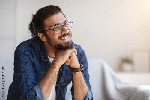 Portrait Of Smiling Indian Man With Eyeglasses And Braces In Home Interior