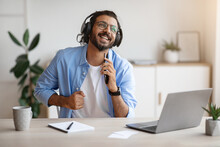 Cheerful Indian Freelancer Guy Singing And Listening Music With Headphones While Working