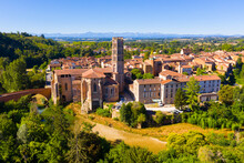 Scenic Aerial View Of Rieux-Volvestre Town On Banks Of Small Tributary Of Garonne In Summer Overlooking Ancient Roman Catholic Cathedral, France