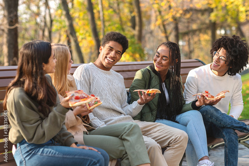 Obraz Black guy making funny jokes, eating pizza with friends - fototapety do salonu