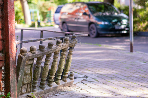 Naklejka premium Old stone balustrades on the streets of the city are askew. The dilapidated fence is in need of repair and restoration