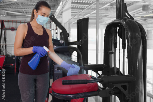 Obraz Woman cleaning exercise equipment with disinfectant spray and cloth in gym - fototapety do salonu