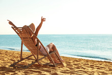 Woman Relaxing On Deck Chair A...