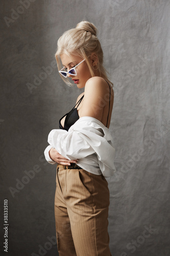 A model girl with perfect blond hair in an unbuttoned shirt and trendy sunglasse Fototapete
