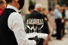 Waiter In Black Mask And Gloves Hold Tray With Glasses Of Champagne. Waiter Holding A Serving Tray Full Of Drinks In Champagne Glasses. Wearing Masks During Coronavirus.
