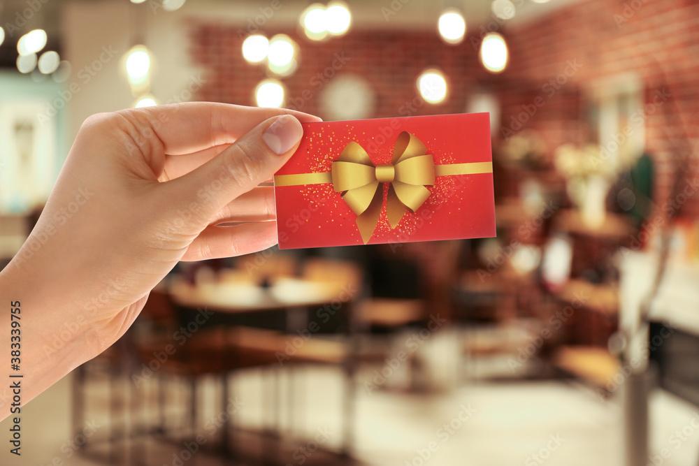 Fototapeta Woman holding gift card in restaurant, closeup