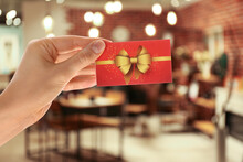 Woman Holding Gift Card In Restaurant, Closeup