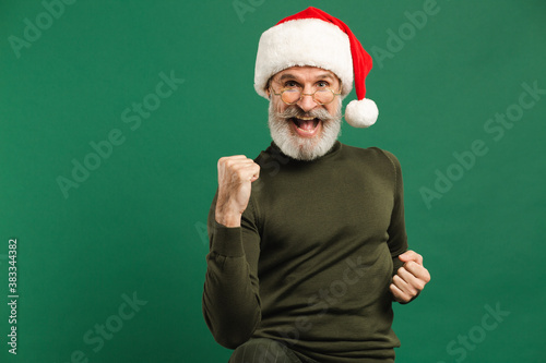 Photographie Happy bearded modern Santa Claus shows a fist of joy on a green background