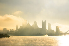 A Foggy, Misty Morning Over The Pittsburgh Ohio River With Bridges And Urban Buildings And Infrastructure.