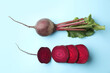 Leinwandbild Motiv Whole and cut fresh red beets on light blue background, flat lay